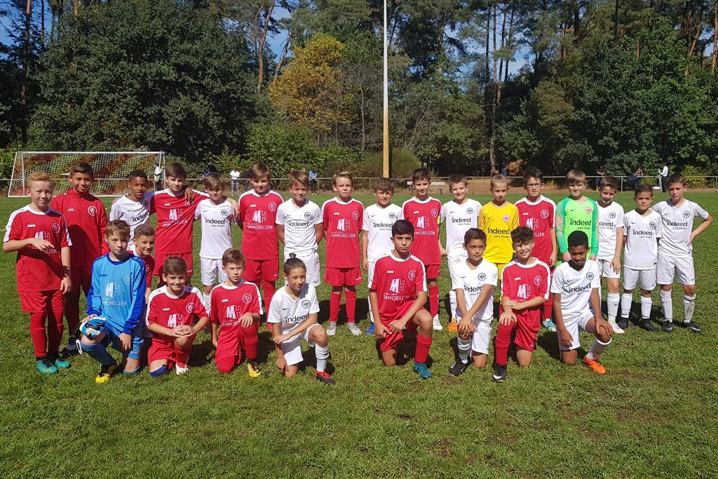 Das Bild zeigt die Langener D1 in den roten Trikots und die Kicker von Eintracht Frankfurt